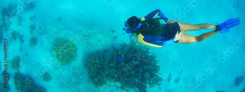 Photo Snorkeller swimming underwater above reef