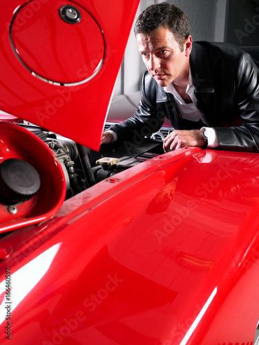 Wallpaper Mural Man watching a V12 motor in a Ferrari.