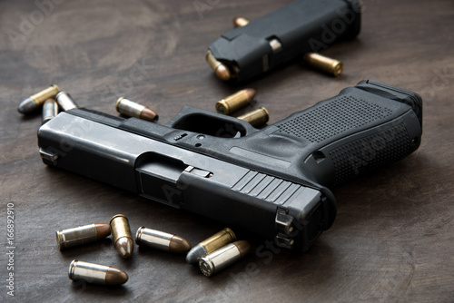 Slika na platnu Gun with ammunition on dark background.