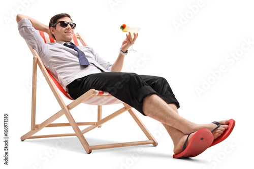 Valokuvatapetti Businessman with a cocktail relaxing in a deck chair