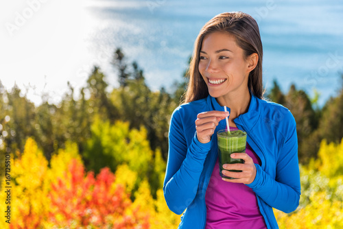 Happy healthy eating girl drinking green smoothie detox outdoors in fall autumn foliage nature retreat. Woman on weight loss diet vegan nutrition cleanse.
