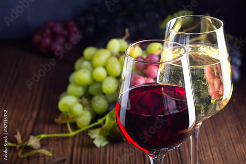 Glasses with red and white wine with grapes on wooden background