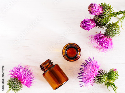 burdock oil in small glass bottle and burdock flowers on white wooden table Fototapeta