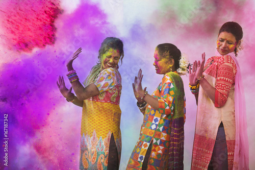 Canvas Print Three Young Indian Women With Colored Face Dancing During Holi Color festival