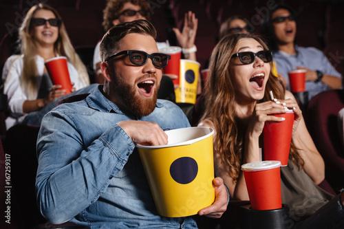 Laughing friends sitting in cinema watch film