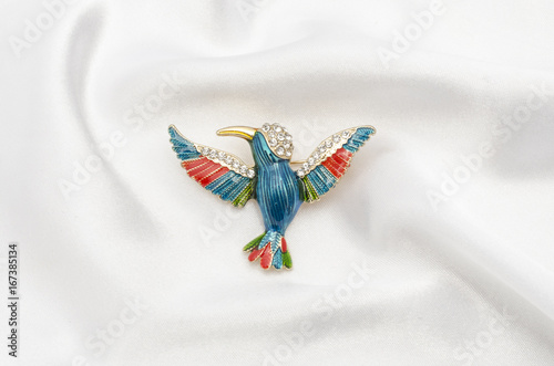 Fotografia enamel brooch with Hummingbird and diamonds on silk fabric
