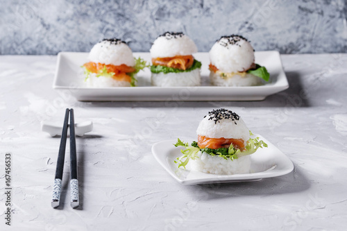 Fotografie, Obraz Mini rice sushi burgers with smoked salmon, green salad and sauces, black sesame served on white square plate with chopsticks over gray concrete background