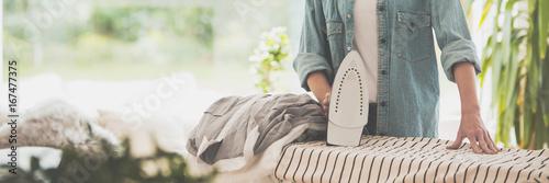 Obraz na plátně Woman ironing clothes