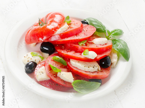 Photo Tomato and mozzarella slices with basil leaves on a white plate.