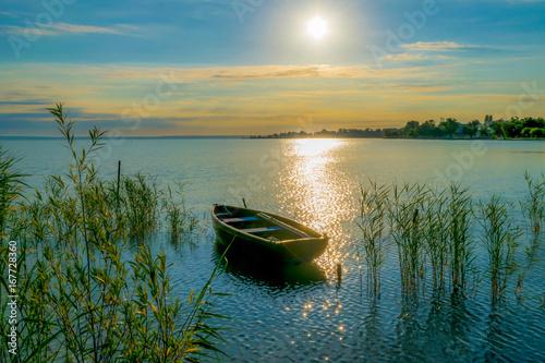 Obraz na plátně Rowing boat on lake at sunset