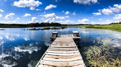 Stary drewniany most nad stawem, błękitne niebo z białymi chmurami odbijają się w tafli wody, na horyzoncie zielona trawa