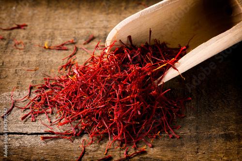saffron threads with spice shovel on wooden background