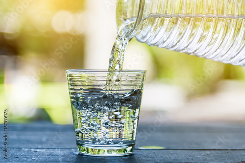 Pour drinking water into the glass. Pour cool drinking water. Ice in glass and drinking water. Clean drinking water.