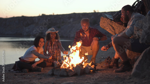 Fotografie, Tablou Group of multiracial people sitting around campfire grilling marshmallows and having fun on coast