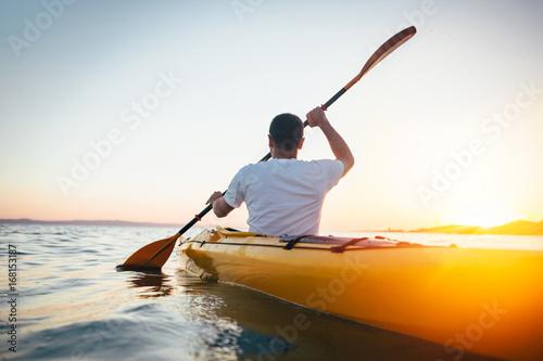 Rear view of man paddling canoe