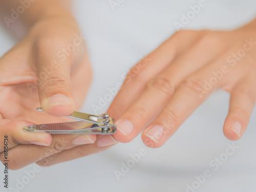 Fotografija Closeup of a woman cutting nails, health care concept.