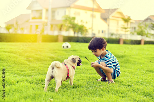 Photographie Happy Asian boy playing with his dog in garden