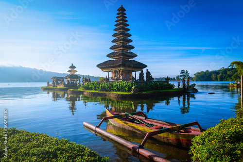 Fototapeta premium Pura Ulun Danu Bratan, Hinduska świątynia z łodzią na Bratan jeziora krajobrazie przy wschodem słońca w Bali, Indonezja.