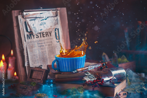 Photo Tea splash in a ceramic cup on a wooden background with candles, mystery newspap