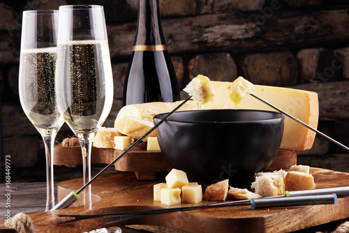 Canvas Print Gourmet Swiss fondue dinner on a winter evening with assorted cheeses on a board