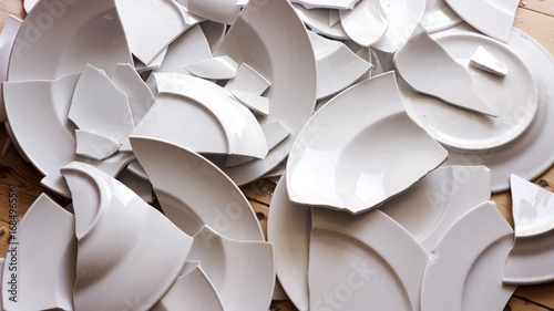 white broken plates on a wooden floor
