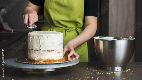 Canvas-taulu Unrecognisable woman decorating a delicious layered sponge cake with icing cream