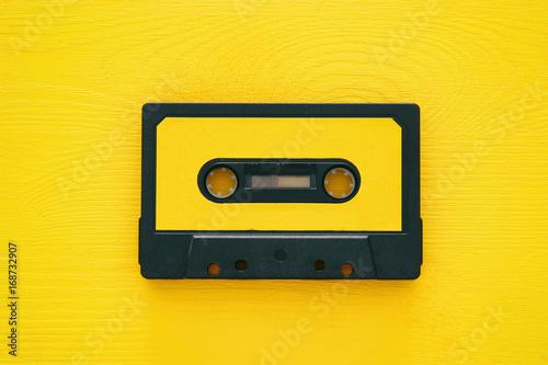 Fotografie, Obraz Retro cassette tape over yellow wooden table. top view.