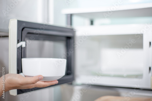 woman hand using are bringing food into the microwave oven at home. To reheat frozen food for their . Cooking made easy concept .