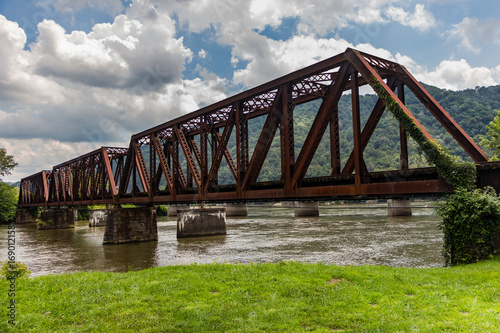Canvas Print Old rusted railroad bridge crossing a river with green grass, mountains in the distance and a cloudy blue sky overhead