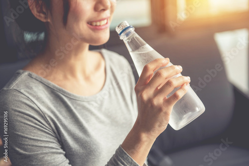 Fotografia Happy woman drinking cold water in morning - Closeup
