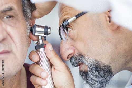 Fotografia Doctor holding otoscope and examining ear of senior man