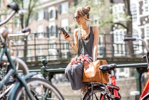 Fototapeta premium Młoda kobieta za pomocą inteligentnego telefonu siedzi z torbą i kwiatami w pobliżu kanału wodnego na starym mieście w Amsterdamie