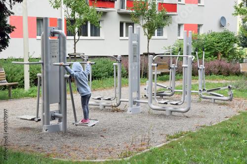 Fototapeta premium Mała dziewczynka ćwiczy w siłowni plenerowej