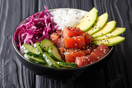 Organic food: tuna poke bowl with rice, fresh cucumbers, red cabbage and avocado close-up. horizontal