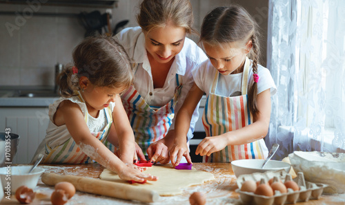Obraz na płótnie Happy family mother and children twins   bake kneading dough in kitchen