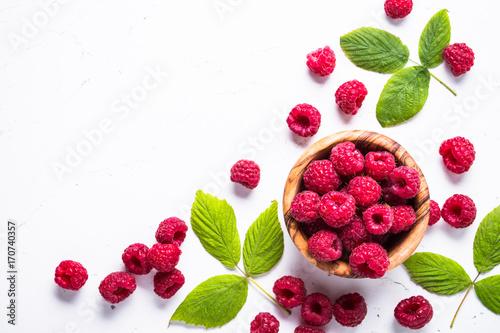 Fotografia Fresh raspberries in wooden bowl on white table. Top view.