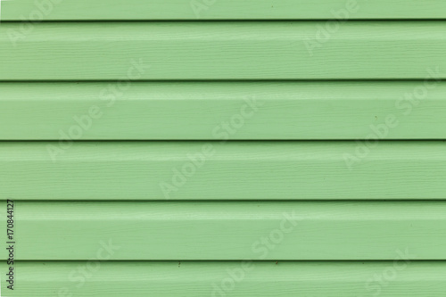 Photo Close up Green vinyl wooden siding panel background with imitation wood texture