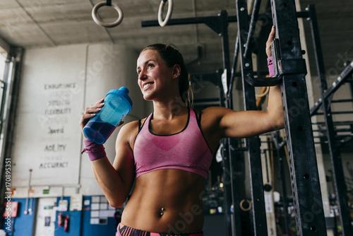 Młoda kobieta pije od butelki podczas gdy pozujący w gym