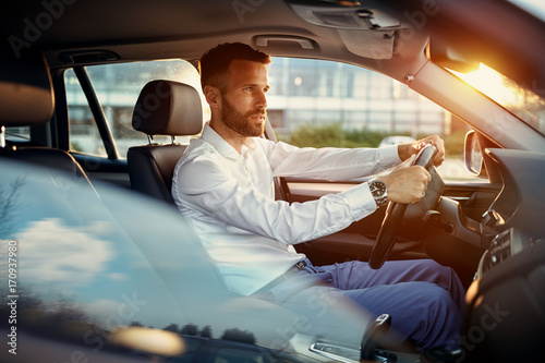 Young businessman driving car. Fototapeta