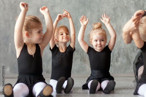 Valokuva little girls ballerina in black dresses, belk tights and pointe shoes sit on the