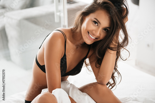 Happy pretty asian woman in sexy lingerie sitting on bed