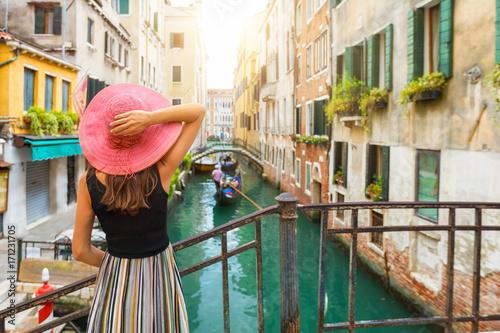 Fototapeta premium Kobieta z czerwonymi słońce kapeluszu spojrzeniami na kanale z gondolą w Wenecja, Włochy