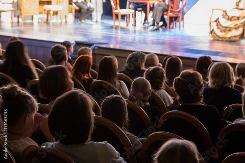 The audience in the theater watching a play. The audience in the hall: adults and children.