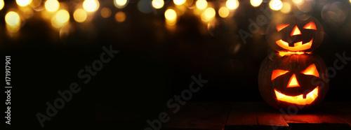 Fotografiet Halloween Pumpkin on wooden table in front of spooky dark background