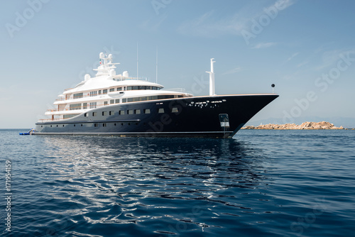 Large luxury motor yacht anchored near rocky island