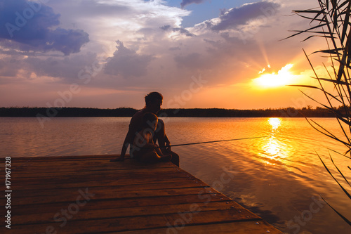 Fotografija Mother and son siting on wooden dock and fishing at sunset.