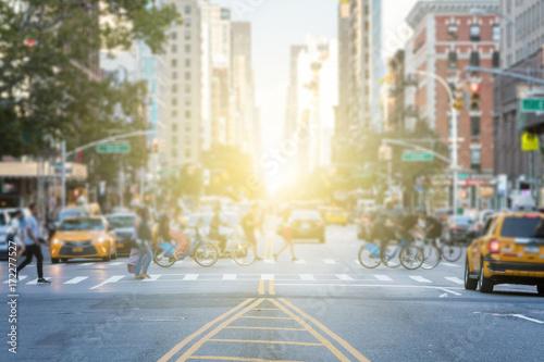 Ludzie przekraczający ruchliwe skrzyżowanie między ruchem na 3rd Avenue i 10th Street na Manhattanie w Nowym Jorku z blaskiem światła słonecznego w tle
