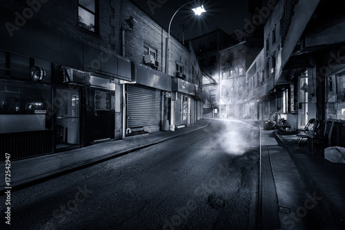 Moody monochrome view of Doyers Street by night, in NYC Chinatown. The bend became known as