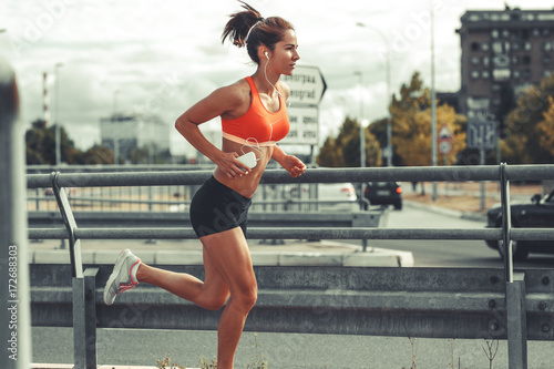 Photo Female runner jogging on the city street by the traffic road