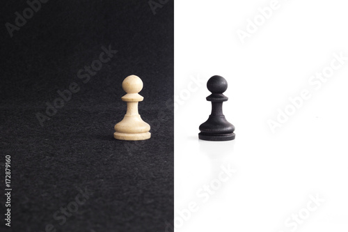 Photo Pair of peon chess peaces confronted as opposites in black and white background